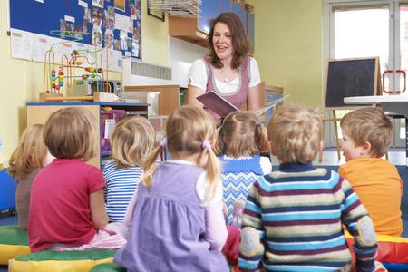 Foto de Group Of Pre School Children Listening To Teacher Reading Story - Imagen libre de derechos