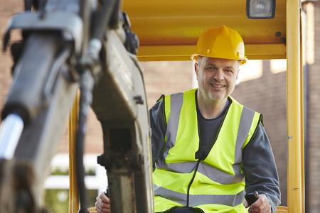 Photo pour Construction Worker Operating Digger On Site - image libre de droit
