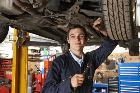 Foto de Apprentice Mechanic Working On Car - Imagen libre de derechos
