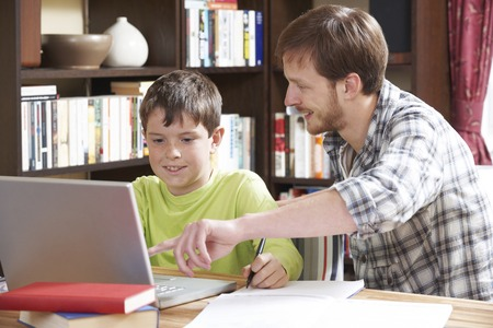 Photo for Boy Studying With Home Tutor - Royalty Free Image
