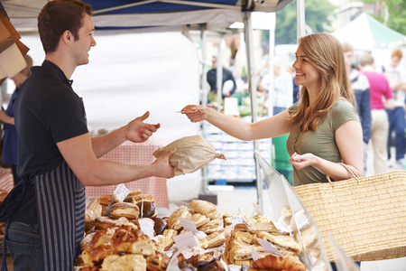 Photo for Woman Buying Bread From Market Stall - Royalty Free Image