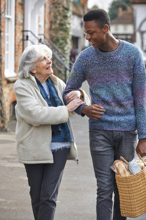 Photo pour Teenage Boy Helping Senior Woman To Carry Shopping - image libre de droit