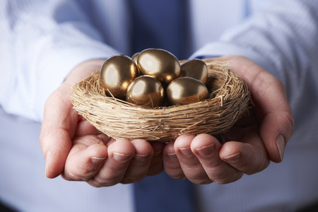 Photo pour Businessman Holding Nest Full Of Golden Eggs - image libre de droit