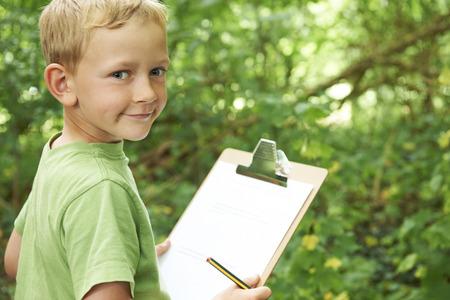 Photo pour Boy Making Notes On School Nature Field Trip - image libre de droit