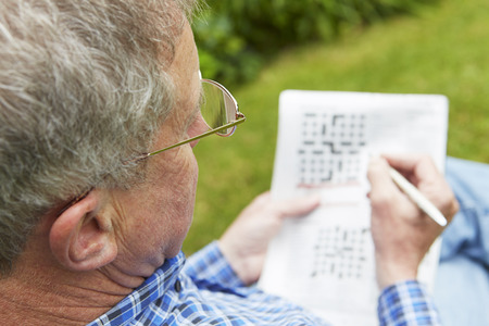Photo pour Senior Man Doing Crossword Puzzle In Garden - image libre de droit