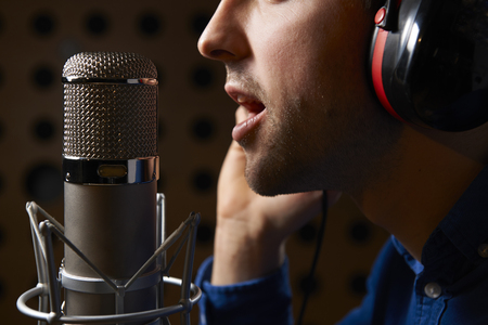 Photo for Male Vocalist Singing Into Microphone In Recording Studio - Royalty Free Image