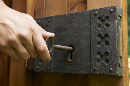 Foto de Hand Turning Key In Old Fashioned Lock - Imagen libre de derechos