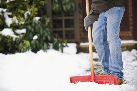 Foto de Man Clearing Snow From Path With Shovel - Imagen libre de derechos