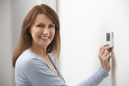 Photo for Smiling Woman Adjusting Thermostat On Home Heating System - Royalty Free Image