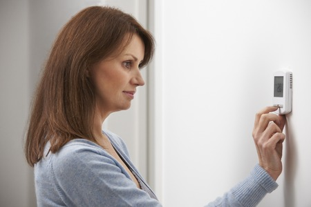 Foto de Woman Adjusting Thermostat On Central Heating - Imagen libre de derechos
