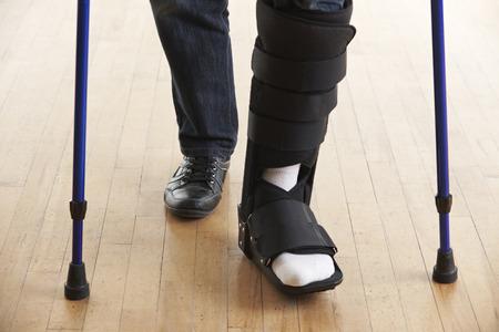 Photo pour Close Up Of Man Walking With Crutches And Cast - image libre de droit