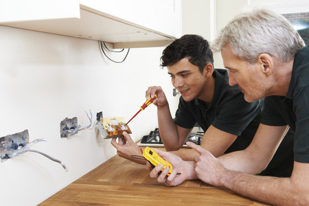 Foto de Electrician With Apprentice Working In New Home - Imagen libre de derechos