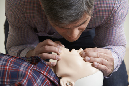 Foto de Man In First Aid Class Performing Mouth To Mouth Resuscitation On Dummy - Imagen libre de derechos