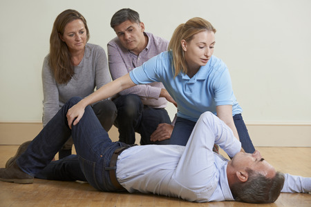 Photo pour Woman Demonstrating Recovery Position In First Aid Training Class - image libre de droit