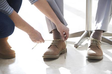 Foto de Adult Daughter Helping Senior Tie Shoelaces - Imagen libre de derechos