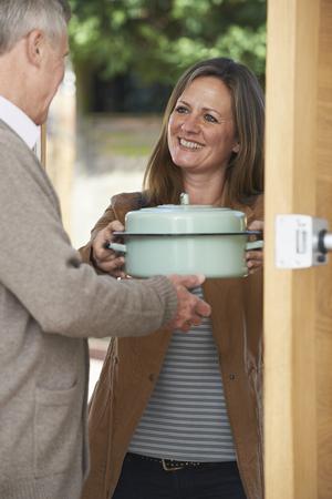 Foto de Woman Bringing Meal For Elderly Neighbour - Imagen libre de derechos