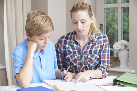 Photo for Female Home Tutor Helping Boy With Studies - Royalty Free Image