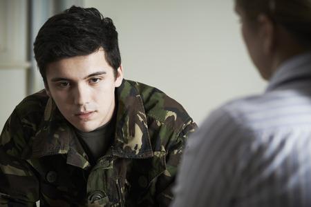 Foto de Soldier Suffering With Stress Talking To Counselor - Imagen libre de derechos