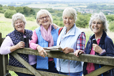 Photo pour Group Of Senior Female Friends Hiking In Countryside - image libre de droit