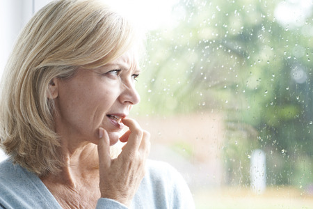 Photo pour Sad Mature Woman Suffering From Agoraphobia Looking Out Of Window - image libre de droit