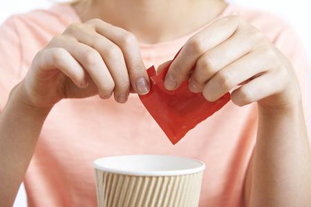 Foto de Woman Adding Artificial Sweetener To Coffee - Imagen libre de derechos