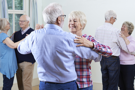 Foto de Group Of Seniors Enjoying Dancing Club Together - Imagen libre de derechos
