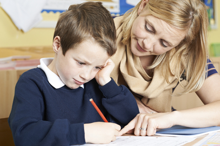 Photo for Teacher With Male Elementary School Pupil With Problem - Royalty Free Image