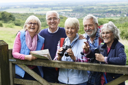 Photo pour Group Of Senior Friends Hiking In Countryside - image libre de droit