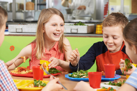 Foto de Group Of Pupils Sitting At Table In School Cafeteria Eating Lunch - Imagen libre de derechos
