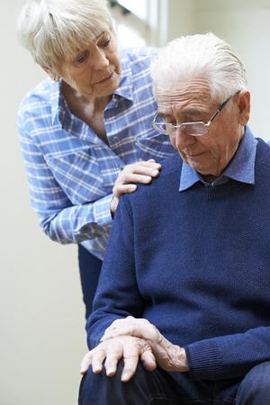 Foto de Senior Woman Comforts Husband Suffering With Parkinsons Diesease - Imagen libre de derechos