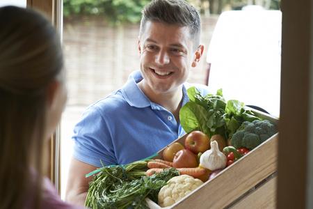 Photo pour Man Making Home Delivery Of Organic Vegetable Box - image libre de droit