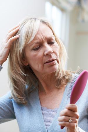 Photo pour Mature Woman With Brush Corncerned About Hair Loss - image libre de droit