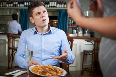 Foto de Customer In Restaurant Complaining To Waitress About Food - Imagen libre de derechos