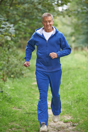 Photo pour Senior Man In Tracksuit Running Through Countryside  - image libre de droit