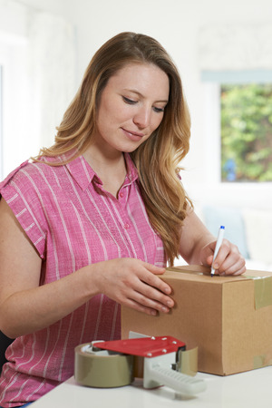 Foto de Woman At Home Writing Address On Package - Imagen libre de derechos