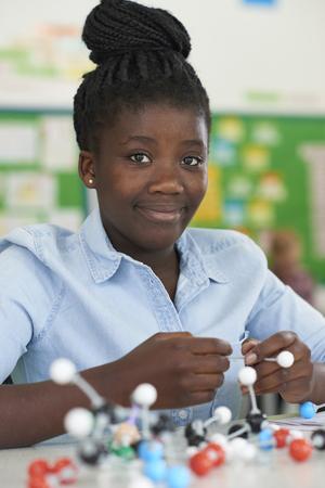 Foto de Female Pupil Using Molecular Model Kit In Science Lesson - Imagen libre de derechos