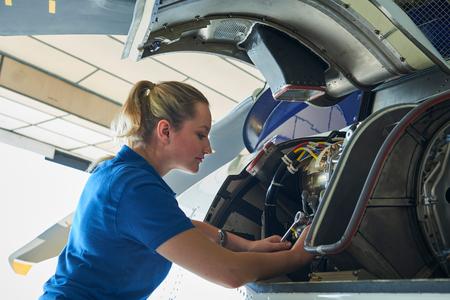 Foto de Female Aero Engineer Working On Helicopter In Hangar - Imagen libre de derechos