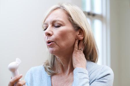 Foto de Mature Woman Experiencing Hot Flush From Menopause - Imagen libre de derechos
