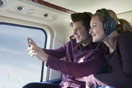 Foto de Couple On Vacation Taking Ride In Helicopter - Imagen libre de derechos