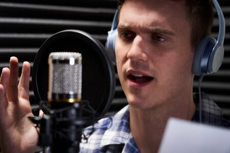 Photo for Man In Recording Studio Talking Into Microphone - Royalty Free Image