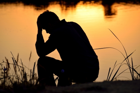 Foto de depressed man sitting against the light reflected in the water - Imagen libre de derechos