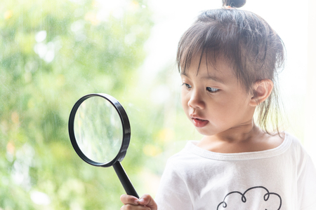 Photo for Asian child girl looking with magnifying glass - Royalty Free Image