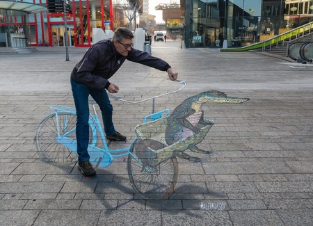 Foto de ALMERE, NETHERLANDS - 27 OCT. 2015: Man showing the power of 3D optical illusion on a street painting of a bicycle in the city of Almere - Imagen libre de derechos