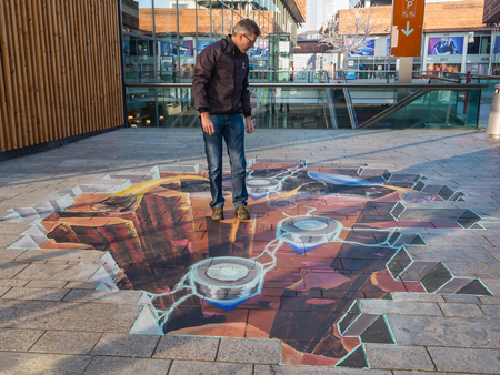 Foto de ALMERE, NETHERLANDS - 27 OCT. 2015: Unknown man shows the power of 3D optical illusion of a street painting by an unknown artist. Once a year the city allows artists to make paintings on the streets - Imagen libre de derechos