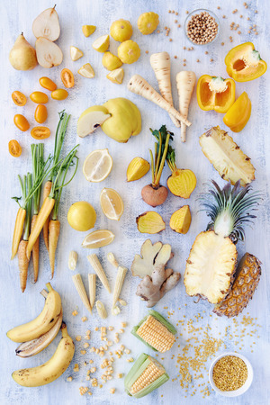 Collection of fresh yellow white toned vegetables and fruits raw produce on white rustic background, capsicum peppers pineapple corn carrot pear quince soya beans legumes lentils ginger parsnip