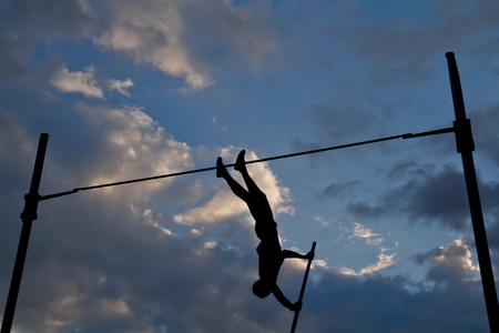 Photo for Silhouette of a pole vaulter against a dramatic cloudscape. - Royalty Free Image