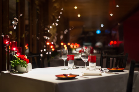Foto de romantic dinner setup, red decoration with candle light in a restaurant. Selective focus. - Imagen libre de derechos