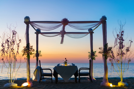 Photo for Romantic dinner setting on the beach at sunset. - Royalty Free Image