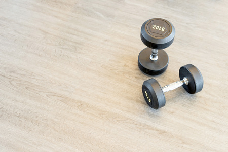 Two dumbbells on the floor in a hall