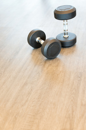 Two dumbbells on the floor in a hall, copy space.